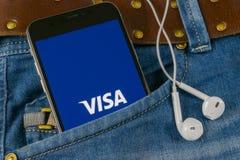在苹果计算机iPhone x屏幕特写镜头的签证申请象在牛仔裤装在口袋里 签证app象 社会媒介app 3d网络照片回报了社交 图库摄影