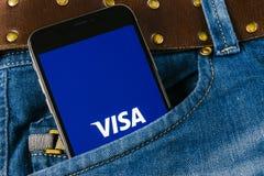在苹果计算机iPhone x屏幕特写镜头的签证申请象在牛仔裤装在口袋里 签证app象 签证线上申请 社会媒介app 免版税库存图片