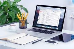 在苹果计算机MacBook屏幕上的谷歌Gmail接口在办公桌上 免版税库存照片