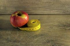在苹果附近被包裹的测量的磁带 免版税库存照片