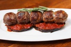 在茄子西红柿酱,调味迷迭香的烤丸子 在一块白色板材,木桌背景的一个盘 关闭 图库摄影