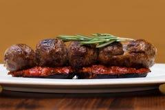 在茄子西红柿酱,迷迭香的烤丸子 在一块白色板材,木桌背景的一个盘 软的特写镜头 免版税库存图片