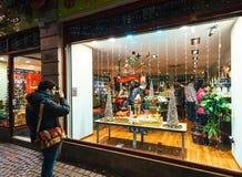 在茶商店茶商店圣诞节前面的人饮用的茶 免版税库存图片