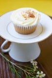 在茶杯立场的红萝卜杯形蛋糕 免版税库存图片