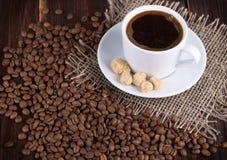 在茶碟和咖啡粒的咖啡杯 免版税库存照片