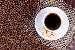 在茶碟和咖啡粒的咖啡杯 库存照片