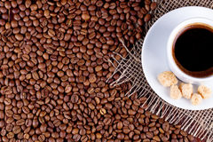 在茶碟和咖啡粒的咖啡杯 免版税库存图片