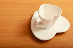 在茶碟的空的茶咖啡杯杯子 重点查出的形状蕃茄白色 免版税图库摄影