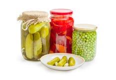 在茶碟的罐装黄瓜反对在瓶子的罐装菜 免版税库存照片