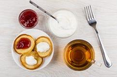 在茶碟的薄煎饼用酸奶干酪,果酱,餐巾,茶 免版税库存图片