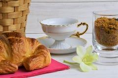 在茶碟,新月形面包,项目篮子,花,在木被绘的背景的红糖的一个空的咖啡杯 库存照片