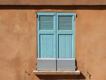 在茶黄墙壁南国家的浅兰的窗口在阳光下 免版税库存照片