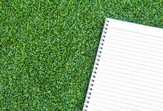 在草上把放的纸笔记本 库存图片