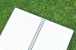 在草上把放的纸笔记本 库存照片