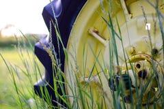 在草叶的老拖拉机轮子后 库存照片