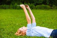 在草和使用片剂的妇女 免版税图库摄影
