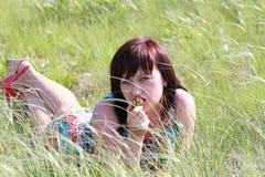 在草和吃草莓的女孩 免版税库存照片