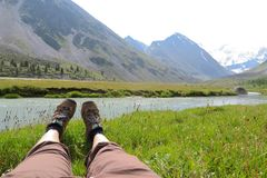在草和山的女性腿在背景环境美化 免版税图库摄影