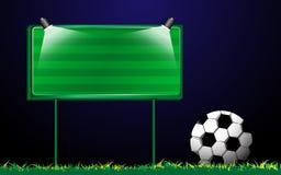 在草和广告牌的橄榄球 图库摄影