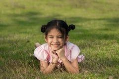 在草和微笑的孩子 免版税库存图片