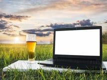 在草和杯的膝上型计算机在日落的冰镇啤酒 自由职业者的想法 图库摄影