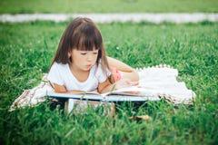 在草和阅读书的小女孩谎言 免版税图库摄影