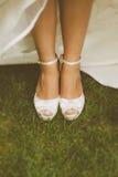 在草地板上的新娘的白色鞋子 库存图片