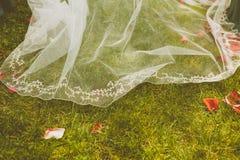 在草地板的新娘的礼服 免版税库存图片