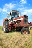 在草地的老农用拖拉机 图库摄影
