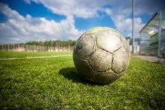 在草地的老足球晴天 免版税图库摄影