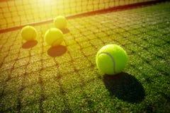 在草地网球场的网球与阳光 免版税图库摄影
