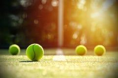 在草地网球场的网球与阳光 图库摄影