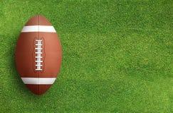在草地背景的橄榄球球 图库摄影