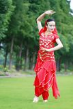 在草坪的亚洲中国秀丽肚皮舞表演者跳舞 免版税图库摄影