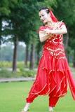 在草坪的亚洲中国秀丽肚皮舞表演者跳舞 库存图片