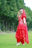 在草坪的亚洲中国秀丽肚皮舞表演者跳舞 图库摄影