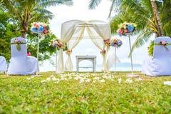在草坪的婚礼曲拱在海滩附近 免版税库存图片
