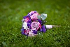 在草坪的婚礼花束 免版税库存图片