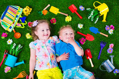 在草坪的孩子有园艺工具的 免版税图库摄影