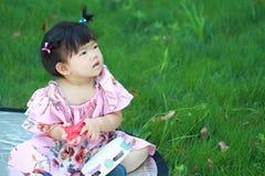 在草坪的逗人喜爱的中国女婴戏剧玻璃 库存图片
