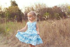 在草坪的滑稽的女孩跳舞 免版税库存照片