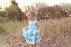 在草坪的滑稽的女孩跳舞 免版税库存图片