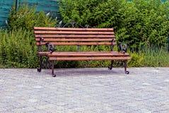 在草坪附近倒空棕色颜色长木凳在边路的 库存图片
