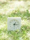 在草坪围场, 1:15一十五的白色简单的时钟 免版税库存照片
