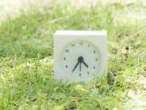 在草坪围场, 4:35四三十五的白色简单的时钟 图库摄影