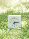 在草坪围场, 7:15的白色简单的时钟七十五 库存照片