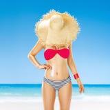 在草帽后的适合的妇女皮在应用太阳奶油的海滨 免版税库存照片