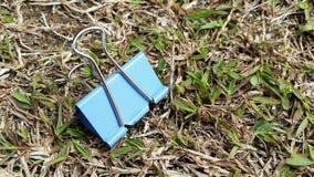 在草持有人的纸夹蓝色 库存图片