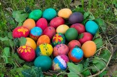 在草掩藏的手画复活节彩蛋 免版税库存照片