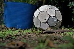 在草放置的老足球 关闭被用完的橄榄球 免版税库存照片